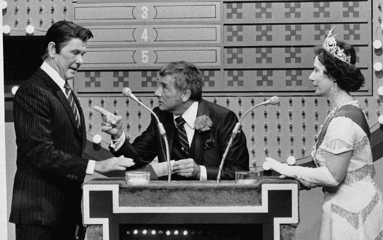 "FILE - In this Nov. 5, 1982 file photo provided by NBC-TV, ""Family Feud"" host Richard Dawson, center, gives President Reagan, played by ""Tonight Show"" host Johnny Carson, a chance at the big money as Queen Elizabeth (Rose Carr) readies herself at the buzzer during ""International Family Feud"" sketch on the show in Burbank, Calif. The ""feud"" pitted the Reagans against the Windsor family. Dawson, the wisecracking British entertainer who was among the schemers in the 1960s sitcom ""Hogan's Heroes"" and a decade later began kissing thousands of female contestants as host of the game show ""Family Feud"" died Saturday, June 2, 2012. He was 79. (AP Photo/NBC-TV, File)"