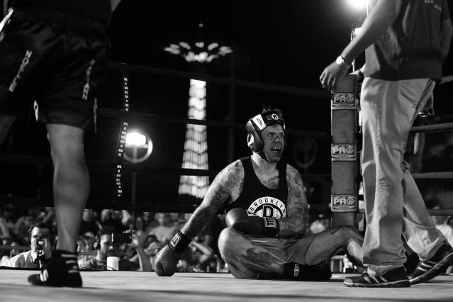 <p>Sgt. John Keigans is knocked to the canvas by opponent Sgt. Billy Polanco during a grudge match at the Brooklyn Smoker in the parking lot of Gargiulo's Italian restaurant in Coney Island, Brooklyn, on Aug. 24, 2017. (Photo: Gordon Donovan/Yahoo News) </p>