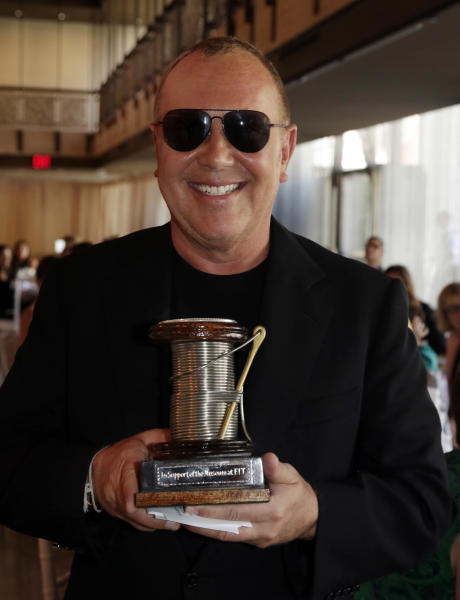 Designer Michael Kors holds 2013 The Couture Council Award for Artistry of Fashion presented by actress Hilary Swank during a luncheon in the David H. Koch Theater of New York's Lincoln Center, Wednesday, Sept. 4, 2013. The luncheon benefits the museum at the Fashion Institute of Technology in New York. (AP Photo/Richard Drew)