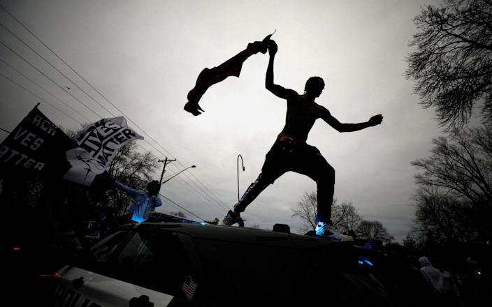 A demonstrator jumps off a police cruiser during a protest after police allegedly shot and killed Daunte Wright - NICHOLAS PFOSI/REUTERS