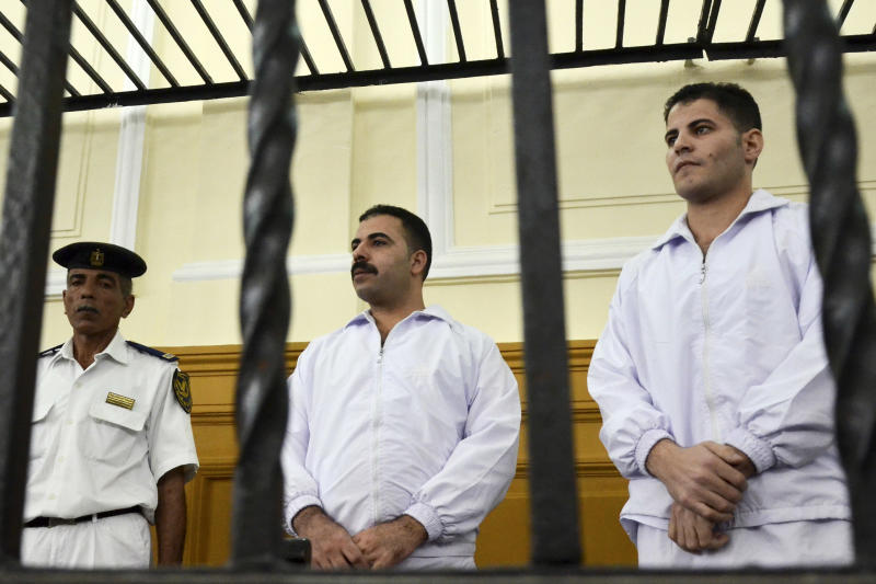 Policemen Awad Ismail, center, and Amin Mahmoud Salah, right, defendants in the beating death of Khaled Said, stand trial in a courtroom in Alexandria, Egypt, Saturday, Sept. 24, 2011.  Two Egyptian policemen charged with brutality in the death of a young Alexandria man are on trial in a case that sparked calls to end what activists describe as rampant police abuses in the country. (AP Photo/Tarek Fawzy)