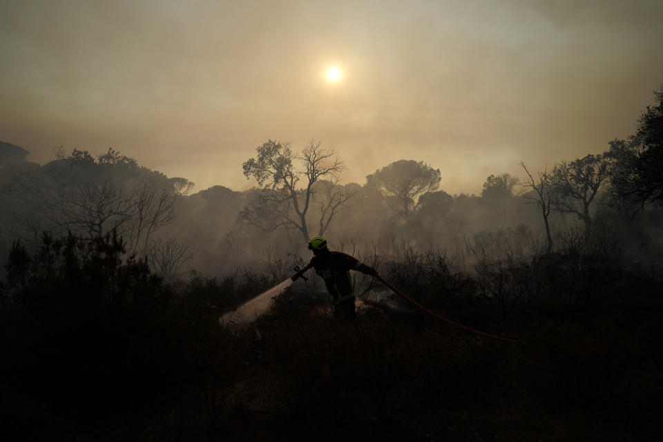A firefighter sprays water from a hose to extinguish a wildfire near Le Luc, southern France, on Wednesday, Aug.18, 2021. A fatal wildfire near the French Riviera was burning out of control in the forests of the popular region, fueled by wind and drought. Over 1,100 firefighters were battling the flames and thousands of tourists and locals were evacuated to safer areas. (AP Photo/Daniel Cole)