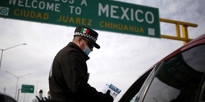 FILE PHOTO: A police officer gives a leaflet with information about coronavirus disease (COVID-19) to a person entering to Mexico from the United States, in Ciudad Juarez, Mexico March 29, 2020. REUTERS/Jose Luis Gonzalez