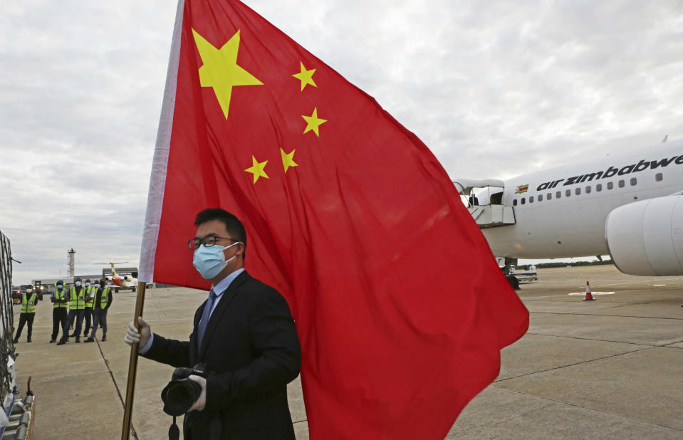 FILE - In this Monday, Feb, 15, 2021 file photo, an official from the Chinese embassy in Zimbabwe holds a Chinese flag next to a plane carrying Sinopharm COVID-19 vaccine from China upon arrival at Robert Mugabe International Airport in Harare. Zimbabwe received its first COVID-19 vaccines with the jet carrying 200,000 Sinopharm doses from China. (AP Photo/Tsvangirayi Mukwazhi)