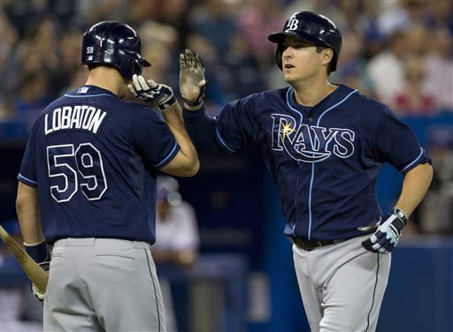Tampa Bay Rays' Kelly Johnson, right, is congratulated by teammate Jose Lobaton after hitting a home run off Toronto Blue Jays starting pitcher Ramon Ortiz during the second inning of a baseball in Toronto on Tuesday May 21, 2013. )AP Photo/The Canadian Press, Frank Gunn)