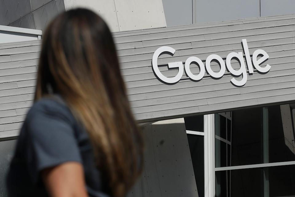 A woman walks below a Google sign on the campus in Mountain View, Calif. on Feb. 2, 2021.