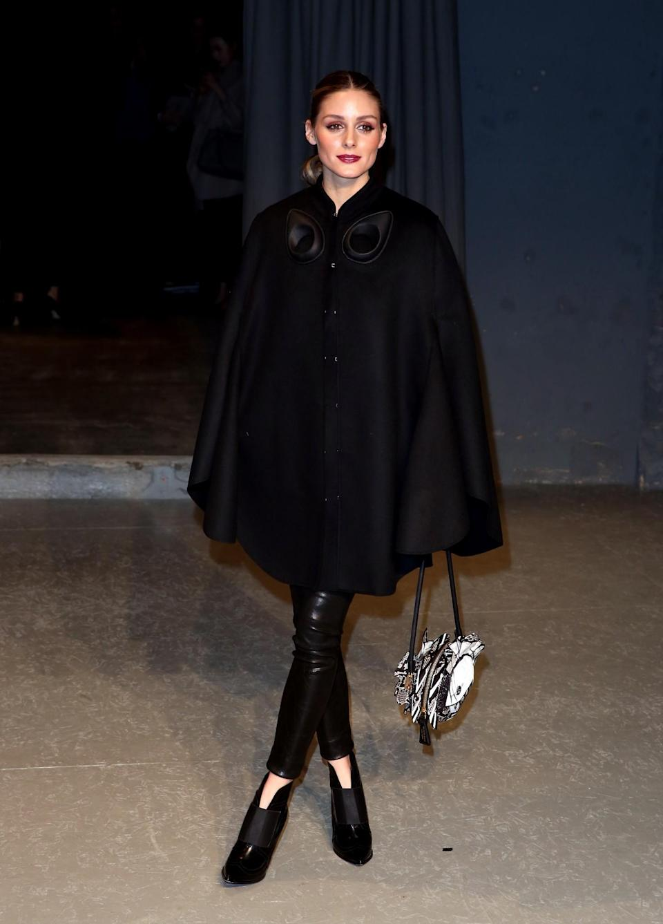 <p>Olivia Palermo went for her usual sleek trousers and Burberry cape combo. <i>[Photo: PA]</i> </p>