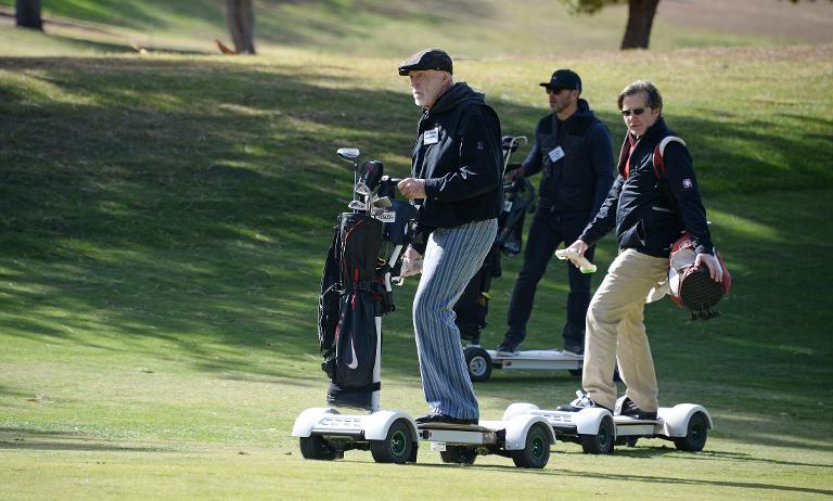 Former European tour player Chris van der Velde (R) and 80-year-old Don Wildman (L), the founder of the Bally Total Fitness chain, ride GolfBoards up the fairway during a golf tournament at the Malibu Golf Club in California, on December 9, 2013