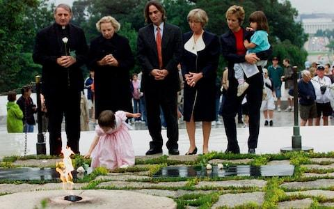 Robert F. Kennedy's granddaughter Saoirse Kennedy Hill places a white rose at the Eternal Flame, President John F. Kennedy's gravesite - Credit: AP