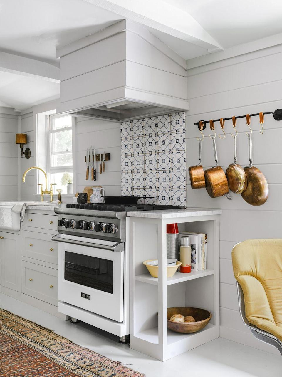 <p>Light cabinets, countertops, and appliances make this tiny 8-by-12-foot galley kitchen look bigger than it is. A hand-painted Portuguese tile backsplash serves up a fresh focal point.</p>