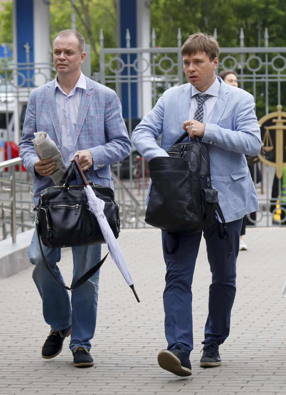 """FILE - In this June 9, 2021 file photo, Russian lawyers Ivan Pavlov, left, and Yevgeny Smirnov arrive to attend a court session in front of Moscow Court in Moscow, Russia. A rights group in Russia announced Sunday July 18, 2021, that it was shutting down, citing fear of prosecution of its members and supporters after Russian authorities blocked its website for allegedly publishing content from an """"undesirable"""" organization. Team 29, including its prominent lawyer Ivan Pavlov, was involved in defending Navalny's foundation in court. In April, Russian authorities launched a criminal case against Pavlov, who is also representing a former Russian journalist accused of treason in a high-profile case, accusing him of disclosing information related to a police investigation. (AP Photo/Alexander Zemlianichenko, File)"""