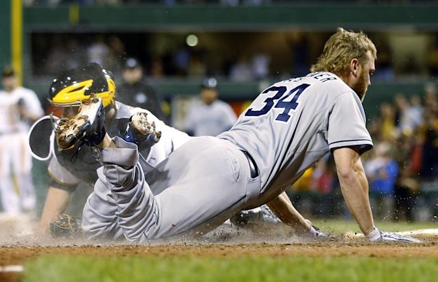 San Diego Padres' Andrew Cashner (34) slides past Pittsburgh Pirates catcher John Buck to score from second on a single by Logan Forsythe in the ninth inning of a baseball game Wednesday, Sept. 18, 2013, in Pittsburgh. The Padres won 3-2. (AP Photo/Keith Srakocic)