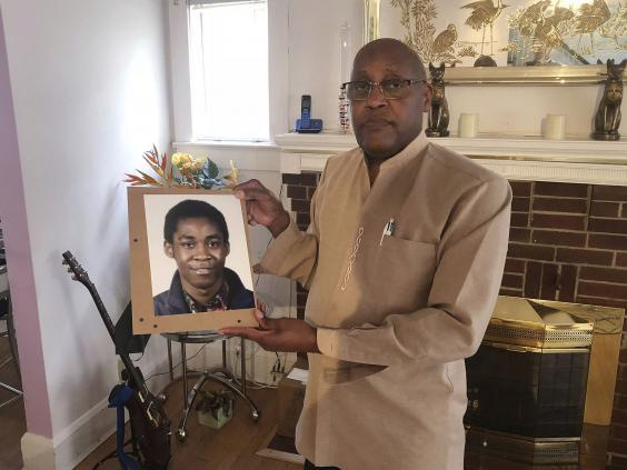 Dia Khafra, father of Askia Khafra, holds a photo of his son in his who died as he was helped Daniel Beckwitt, dig tunnels for a nuclear bunker beneath his Maryland home (AP)