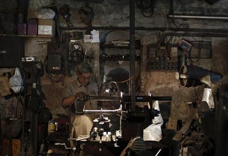 A worker makes parts of a drilling machine at a workshop in the old quarters of Delhi November 12, 2013. REUTERS/Adnan Abidi/Files