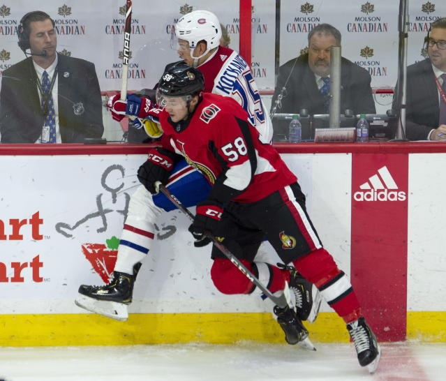 Ottawa Senators defenseman Maxime Lajoie collides with Montreal Canadiens center Jesperi Kotkaniemi along the boards during the second period of an NHL game in Ottawa, Ontario, Saturday, Oct. 20, 2018. (Adrian Wyld/The Canadian Press via AP)