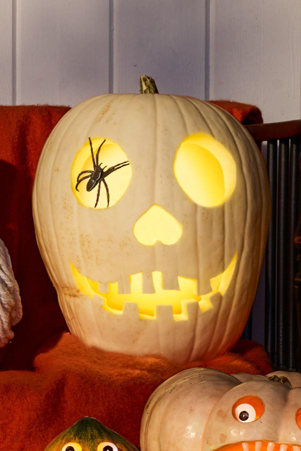 "<p>After you carve a bony facial expression, stick a plastic spider in one socket. On a tall white pumpkin, trace a circle around plastic spider and cut out. Carve a second circle eye, triangle nose, and jagged teeth. Push spider into 1 eyehole.<br></p><p><strong>What You'll Need: </strong><a href=""https://www.amazon.com/dp/B07CVJ3LBN/?tag=syn-yahoo-20&ascsubtag=%5Bartid%7C10070.g.950%5Bsrc%7Cyahoo-us"" rel=""nofollow noopener"" target=""_blank"" data-ylk=""slk:Plastic spider"" class=""link rapid-noclick-resp"">Plastic spider</a> ($9 for 30, Amazon)</p>"