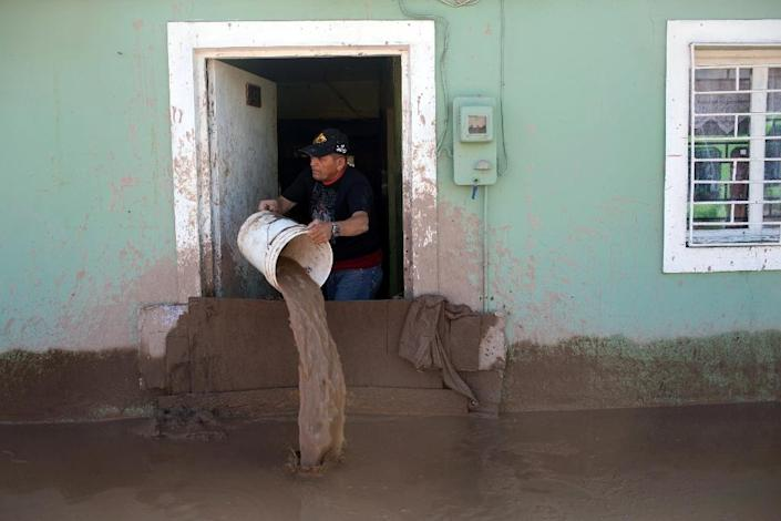 A man empties his home flooded by heavy rainfall, in Copiapo, Chile on March 26, 2015 (AFP Photo/Pablo Sanhueza)