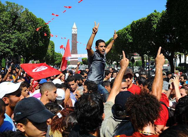 Protesters gather on the main avenue of Tunis after the leader of a leftist Tunisian opposition party, Mohammed Brahmi, was gunned down as he left home, in Tunisia, Thursday, July 25, 2013. Brahmi, 58, of an Arab nationalist political party was in his car outside home when gunmen fired several shots at him, said Interior Ministry spokesman Mohammed Ali Aroui. It is the second killing of an opposition member this year, following that of Chokri Belaid, a member of the same leftist Popular Front coalition as Brahmi. Belaid was also shot dead in his car outside his home in February. His killing provoked a political crisis that nearly derailed Tunisia's political transition. (AP Photo/Hassene Dridi)