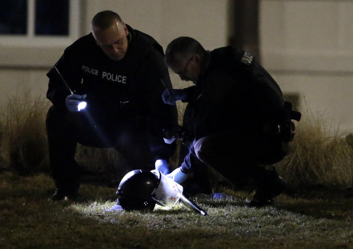 Police shine a light on a helmet as they investigate the scene where two officers were shot outside the Ferguson Police Department on March 12. (AP/Jeff Roberson)