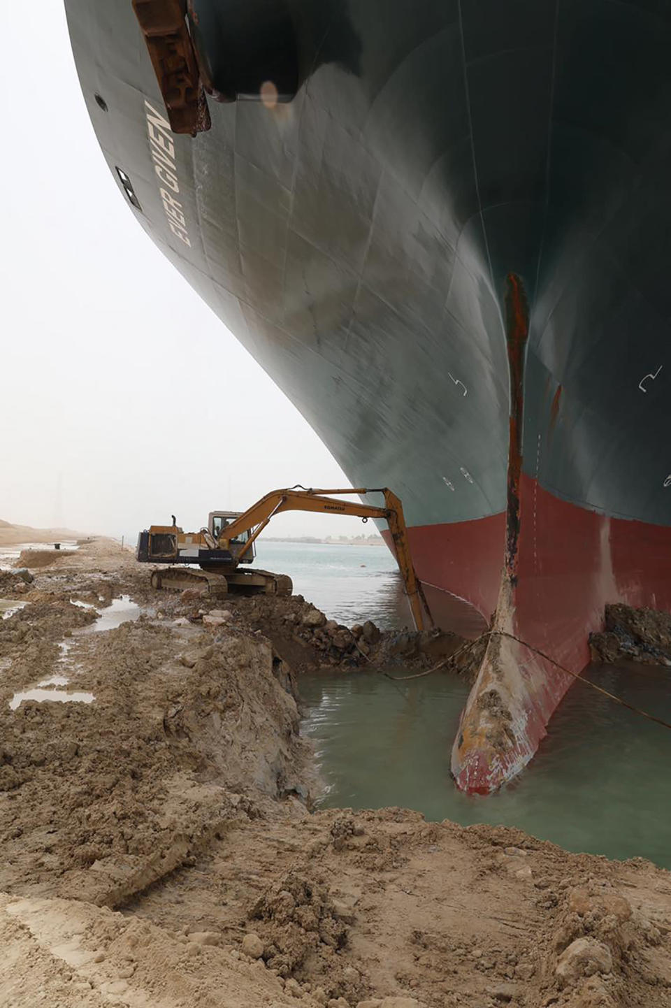 This photo released by the Suez Canal Authority on Thursday, March 25, 2021, shows a backhoe trying to dig out the keel of the Ever Given, a Panama-flagged cargo ship, that is wedged across the Suez Canal and blocking traffic in the vital waterway. An operation is underway to try to work free the ship, which further imperiled global shipping Thursday as at least 150 other vessels needing to pass through the crucial waterway idled waiting for the obstruction to clear. (Suez Canal Authority via AP)