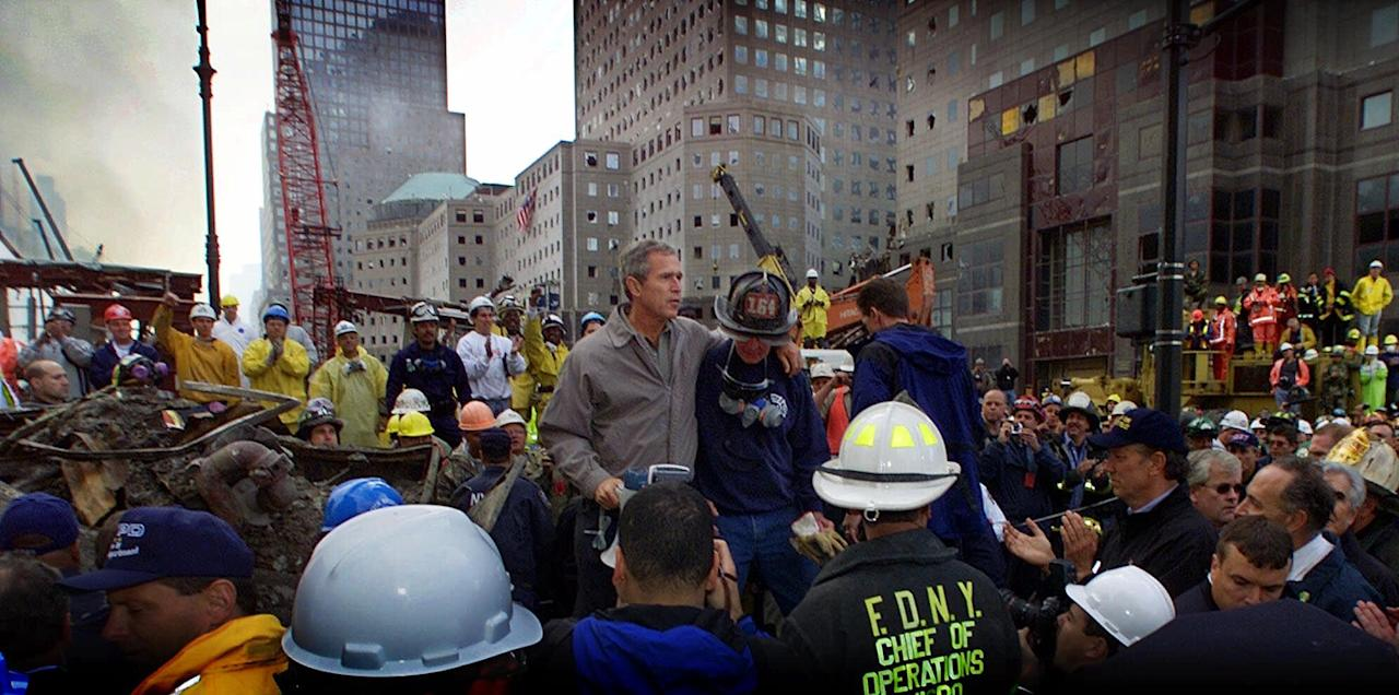 President Bush is surrounded by fire fighters while standing in front of the World Trade Center during a tour of the devastation, Friday, September 14, 2001. Bush is standing on a burned fire truck. Mayor Giuliani said 4,763 people had been reported missing in the devastation of the World Trade Center. (AP Photo/Doug Mills)