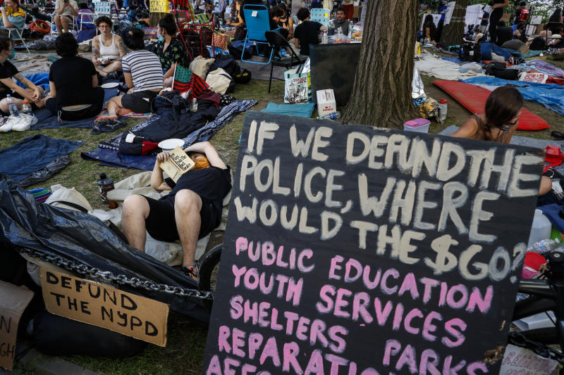 Protesters occupy an encampment outside City Hall beside signs calling for the defunding of police, Friday, June 26, 2020, in New York. (AP Photo/John Minchillo)