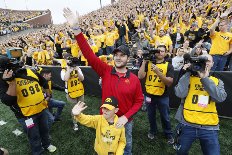 Carson King, of Altoona, Iowa, center, waves to patients in the University of Iowa Stead Family Children's Hospital at the end of the first quarter of an NCAA college football game between Iowa and Middle Tennessee, Saturday, Sept. 28, 2019, in Iowa City, Iowa. King plans to donate more than $1 million to charity after his decision to display a hand-written sign before the Sept. 14 Iowa State-Iowa football game seeking money for beer prompted an overwhelming number of donations. (AP Photo/Charlie Neibergall)