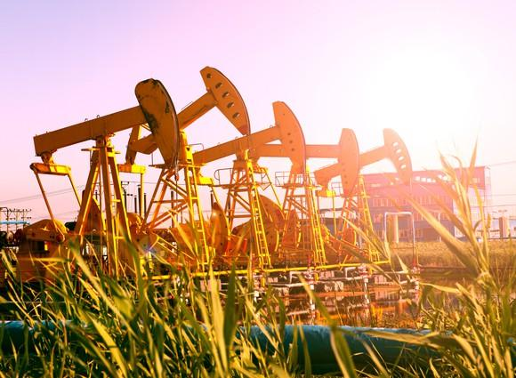 Several pumpjacks in a row with sunburst.