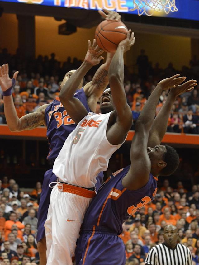 Syracuse's C.J. Fair, center, tries to score against Clemson's K. J. McDaniels, left, and Landry Nnoko during the second half of an NCAA college basketball game in Syracuse, N.Y., Sunday, Feb. 9, 2014. Syracuse won 57-44. (AP Photo/Kevin Rivoli)
