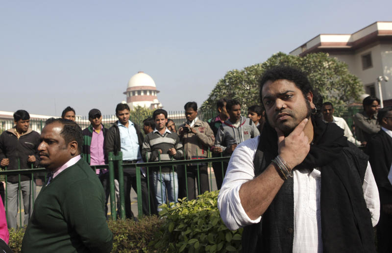 Indian gay rights activists and others stand outside the Supreme Court after the top court ruled that a colonial-era law criminalizing homosexuality will remain in effect in India in New Delhi, India, Wednesday, Dec. 11, 2013. The Supreme Court threw out a 2009 New Delhi High Court decision that struck down the law as unconstitutional, dealing a blow to gay activists who have argued for years for the chance to live openly in India's deeply conservative society. The top court said it was for lawmakers and not the courts to decide the matter. (AP Photo/Tsering Topgyal)