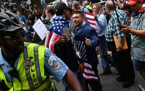 Police escort 'Unite the Right' organiser Jason Kessler and protesters during a far-right rally at Lafayette Park opposite the White House - Credit: AFP