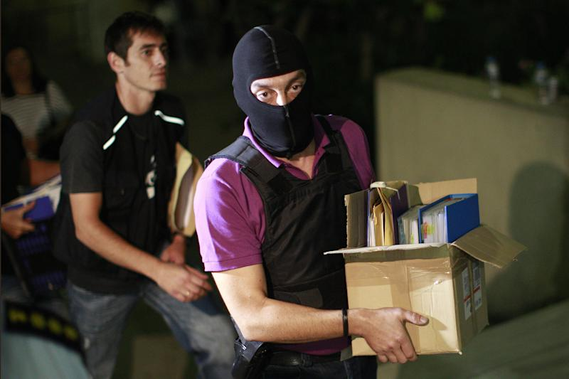 An anti-terror police officer carries a box containing the case file against the arrested suspects of the extreme far-right Golden Dawn party as he arrives at the court in Athens, Saturday, Sept. 28, 2013. Police arrested the leader of Greece's extreme-right Golden Dawn party and other top members on Saturday, in an escalation of a government crackdown after a fatal stabbing allegedly committed by a supporter. It is the first time since 1974 that sitting members of Parliament have been arrested. (AP Photo/Kostas Tsironis)