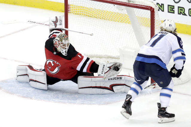 New Jersey Devils goaltender Keith Kinkaid, left, makes a save on a shot by Winnipeg Jets left wing Kyle Connor during overtime of an NHL hockey game, Saturday, Dec. 1, 2018, in Newark, N.J. (AP Photo/Julio Cortez)