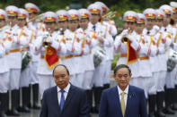 Japanese Prime Minister Yoshihide Suga, right, and his Vietnamese counterpart Nguyen Xuan Phuc, left, attend a welcoming ceremony at the Presidential Palace in Hanoi, Vietnam Monday, Oct. 19, 2020. (Kham/Pool Photo via AP)