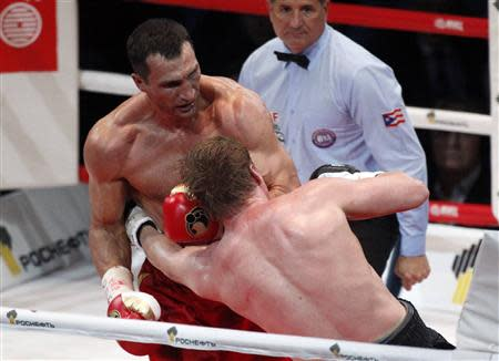 Heavyweight world champion Vladimir Klitschko (L) of Ukraine and challenger Alexander Povetkin of Russia exchange punches during their heavyweight title fight in Moscow October 6, 2013. REUTERS/Maxim Shemetov