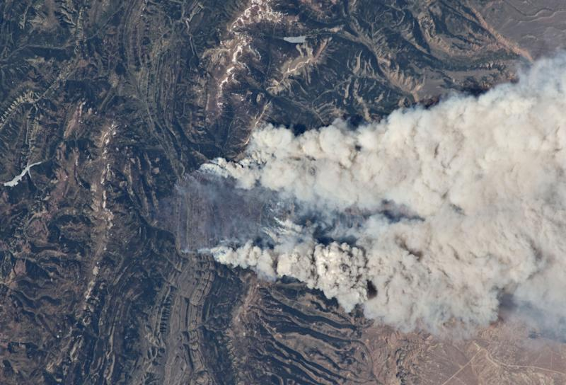 This image provided by NASA taken by an Expedition 31 crew member Wednesday June 27, 2012 aboard the International Space Station, flying approximately 240 miles above Earth, recorded a series of images of the current wild fires in the southwestern United States. These particular fires, of unknown cause, are burning at the south end of the Wyoming Range in southwestern Wyoming, and have affected 17,000 acres. The fires have produced two major smoke plumes (center) that dominate the image. The fires are occurring 120 miles due south of Yellowstone Lake which appears as an irregular blue shape (upper right --if the image is oriented with north toward the top right corner). Utah's Great Salt Lake (image far left) is about 120 miles away. Winds transport the smoke in a northeasterly direction: the plumes can be seen to cross the Wind River Range (center), blowing directly toward the Big Horn Mts., which appear as a dark, curved feature (lower right). This 180mm image spans a wide area from northern Utah (left) to northeastern Montana (right). (AP Photo/NASA)