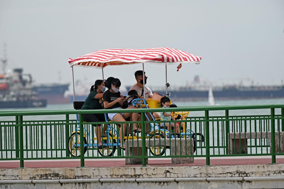 A family ride a multi-cycle along the jetty at Eastcoast park beach in Singapore on April 1, 2021. (Photo by ROSLAN RAHMAN / AFP) (Photo by ROSLAN RAHMAN/AFP via Getty Images)