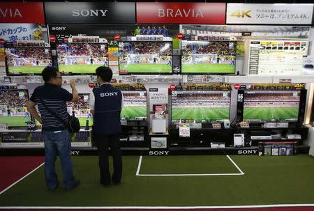 A shopper looks at Sony Corp's Bravia television sets screening a soccer match at an electronics retail store in Tokyo