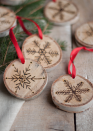 "<p>Using an etching tool, draw a small snowflake onto wood slices. Tie on a red ribbon to complete the look.</p><p><strong>Get the tutorial at <a href=""http://www.designmom.com/2013/11/the-perfect-gift-etched-snowflake-ornaments-in-birch/#comments"" rel=""nofollow noopener"" target=""_blank"" data-ylk=""slk:Design Mom"" class=""link rapid-noclick-resp"">Design Mom</a>.</strong></p><p><a class=""link rapid-noclick-resp"" href=""https://www.amazon.com/Assorted-Decorations-Ornaments-Super-Outlet/dp/B01FRDI8EY/?tag=syn-yahoo-20&ascsubtag=%5Bartid%7C10050.g.1070%5Bsrc%7Cyahoo-us"" rel=""nofollow noopener"" target=""_blank"" data-ylk=""slk:SHOP WOOD SLICES"">SHOP WOOD SLICES</a></p>"