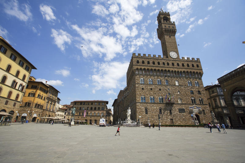 People walk in an unusually uncrowded historical Piazza della Signoria square, in Florence, Italy, Wednesday, June 3, 2020. The Uffizi museum reopened to the public after over two months of closure due to coronavirus restrictions. (AP Photo/Andrew Medichini)