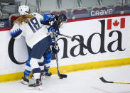 Finland's Jenni Hiirikoski, right, is checked by Jesse Compher, of the United States, during the first period of an IIHF women's hockey championships semifinal in Calgary, Alberta, Monday, Aug. 30, 2021. (Jeff McIntosh/The Canadian Press via AP)