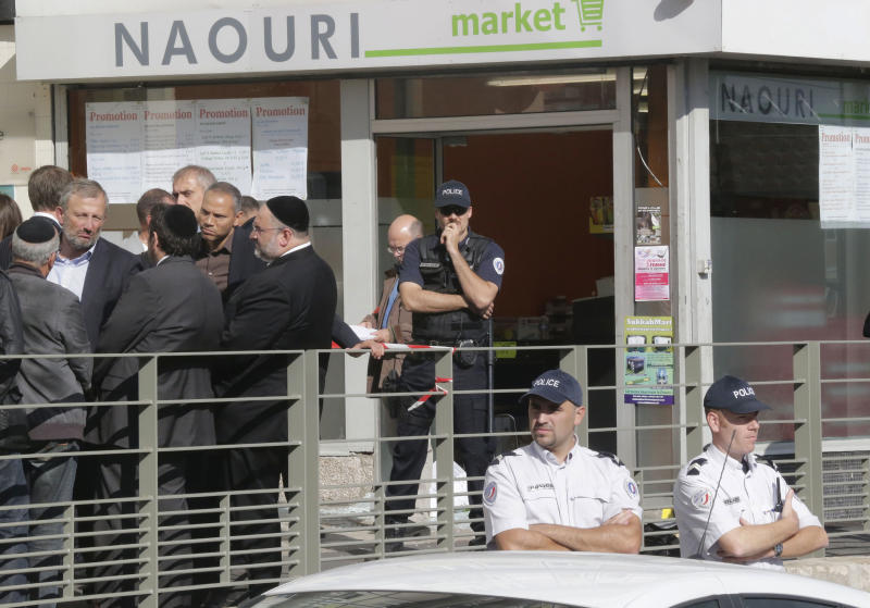 Mayor of Sarcelles, Francois Pupponi, 2nd left facing, and Rabbi of Sacelles Rav Chalom Berros, top 3rd right, talks with members of the Jewish community in front of the kosher grocery store where a bomb exploded in Sarcelles, north of Paris, Wednesday, Sept. 19, 2012. Four people where injured when a small package bomb exploded inside a kosher grocery store in Sarcelles a Paris suburb. (AP Photo/Michel Euler)