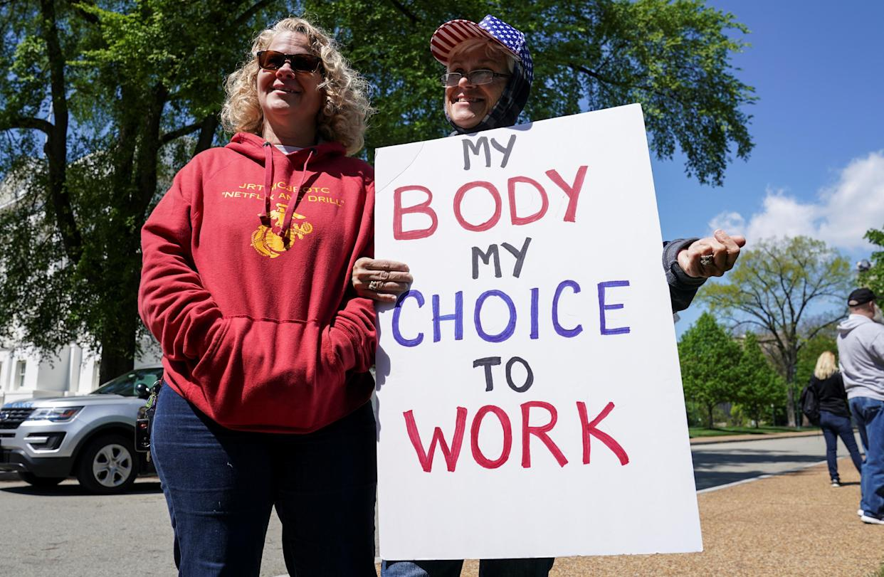 Demonstrators gather with a sign saying