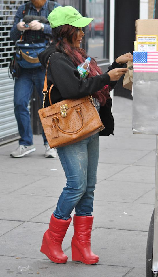Snooki is seen buying a hot dog in Jersey City wearing bright red moon boot wedges on March 21, 2012.