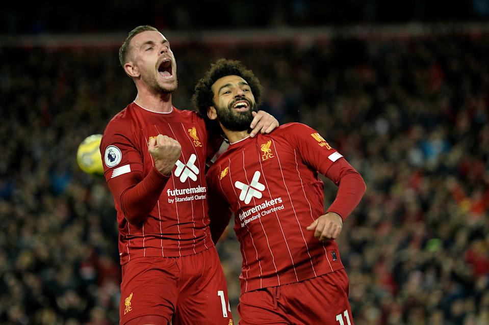 Liverpool's Egyptian midfielder Mohamed Salah (R) celebrates with Liverpool's English midfielder Jordan Henderson after scoring a penalty during the English Premier League football match between Liverpool and Tottenham Hotspur at Anfield in Liverpool, north west England on October 27, 2019. (Photo by STRINGER / AFP) / RESTRICTED TO EDITORIAL USE. No use with unauthorized audio, video, data, fixture lists, club/league logos or 'live' services. Online in-match use limited to 120 images. An additional 40 images may be used in extra time. No video emulation. Social media in-match use limited to 120 images. An additional 40 images may be used in extra time. No use in betting publications, games or single club/league/player publications. /  (Photo by STRINGER/AFP via Getty Images)
