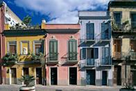 <p>Pale pastel row houses soak up the warm Italian sun in Sardinia.</p>