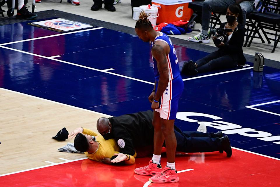 A fan is tackled by security on the floor as Dwight Howard looks on in the second half of Game 4 of the 76ers-Wizards playoff series at Capital One Arena.