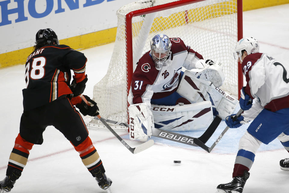 Colorado Avalanche goalie Philipp Grubauer (31) and forward Nathan MacKinnon (29) defend as Anaheim Ducks forward Derek Grant (38) shoots during the second period of an NHL hockey game in Anaheim, Calif., Friday, Jan. 22, 2021. (AP Photo/Ringo H.W. Chiu)
