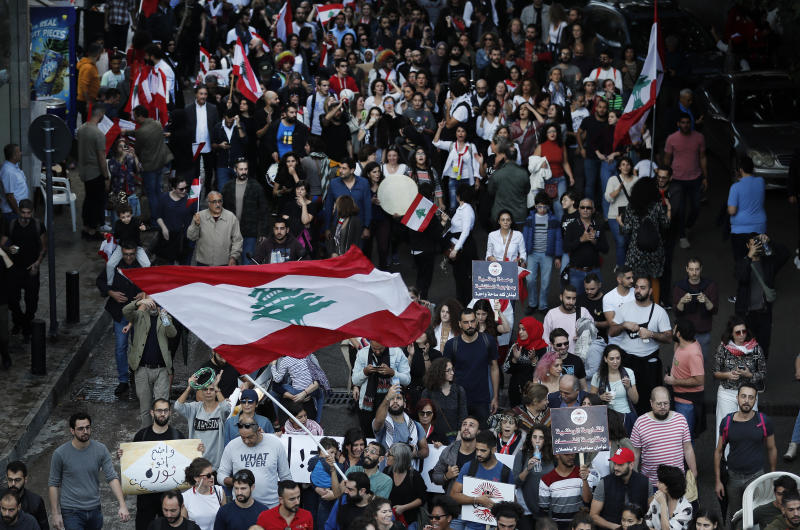 Lebanese protesters wave their national flag, as they march in Beirut, Lebanon, Sunday, Dec. 1, 2019. Protesters have been holding demonstrations since Oct. 17 demanding an end to widespread corruption and mismanagement by the political class that has ruled the country for three decades. (AP Photo/Hussein Malla)