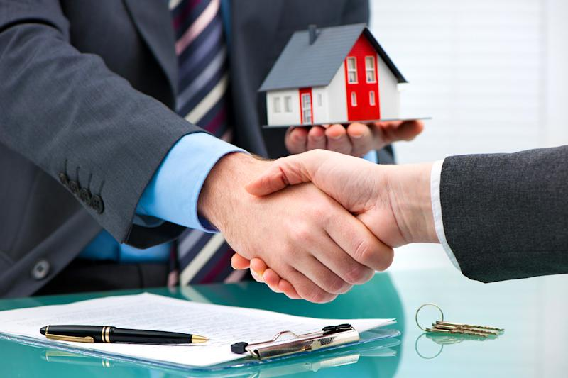 Two men in suits shaking hands after a contract signing, with one holding a miniature house in his left hand.